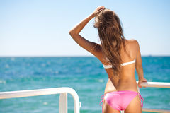 Back woman on the seashore in bikini Stock Photos