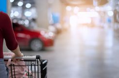 Back of woman with shopping cart move and look for her car in ca stock photography