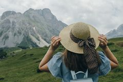 Back of a Woman traveler with blue backpack holding hat and look. Ing forward at  houses Stock Photos