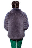 Back of a woman in a violet fur coat made of arctic fox and gree Royalty Free Stock Image