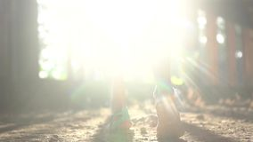 Back of woman walking in abandoned building through sunlight rays. Closeup female legs walking in abandoned building through sunlight rays - video in slow motion stock video footage