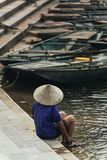 Back of woman wearing purple shirt, conical hat carry wash her feet in the river with empty rowing boats in the background. At Trang An Grottoes in Ninh Binh Stock Image