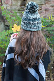 Back of a womans head wearing a pom pom hat Royalty Free Stock Photos
