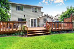 Back yard house exterior with spacious wooden deck. With patio area and attached pergola. Northwest, USA royalty free stock photos