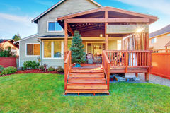 Back yard house exterior with wooden walkout deck royalty free stock images