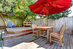 Back yard large deck with red umbrella and chairs. Royalty Free Stock Photography