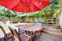 Back yard large deck with red umbrella and chairs. Royalty Free Stock Photos