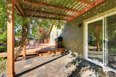 Back yard with pergola , tile floor and wooden walkout deck Royalty Free Stock Photos