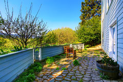Back yard with stone tile floor, patio area and flower beds Royalty Free Stock Photos