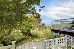 Back yard white fence and deck with water view. Royalty Free Stock Photos