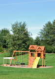 Back Yard Wooden Swing Set. On Green Lawn royalty free stock images