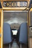 Yellow-orange and black school bus with wide open emergency back door stock photo