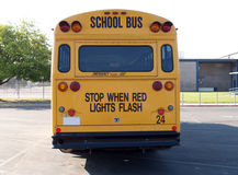 Back of yellow school bus in parking lot Stock Images