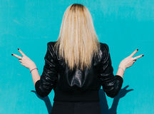 Back of a young beautiful blonde girl on the background of turquoise wall sunny summer day shows victory sign, outdoor, filter. Royalty Free Stock Images