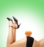 Back of a young and beautiful woman with an orange Royalty Free Stock Photos