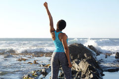Back of young black woman looking out at sea with hand raised Royalty Free Stock Photography