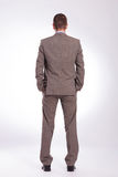 Back of a young business man with both hands in pockets. Full length back view picture of a young business man standing with both hands in his pockets. on a gray Royalty Free Stock Images