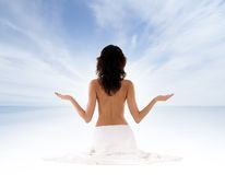 Back of a young and fit meditating brunette Royalty Free Stock Photos