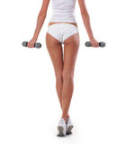 Back of a young and fit woman holding dumbbells Royalty Free Stock Images