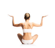 Back of a young and fit woman meditating on white Royalty Free Stock Images