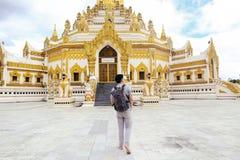 Back of young man backpacker walking towards Burmese temple name. D Buddha Relic Tooth Pagoda in Yangon, Myanmar stock image