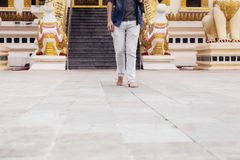 Back of young man backpacker walking towards Burmese temple named Buddha Relic Tooth Pagoda in Yangon, Myanmar.  royalty free stock photo