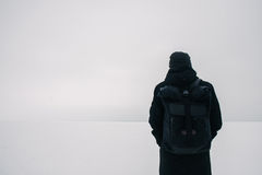 Back young man with a black backpack, traveling on snow-covered winter places. Back hipster young man with a black backpack, traveling in winter on the frozen Stock Image