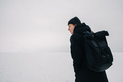 Back young man with a black backpack, traveling on snow-covered winter places. Back hipster young man with a black backpack, traveling in winter on the frozen Royalty Free Stock Photos