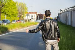 Back of young man, hitchhiker waiting on roadside. Back of young man, a hitchhiker waiting for car on roadside in city, wearing black leather jacket Royalty Free Stock Photography