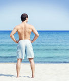 Back of a young man posing on the beach. Young, fit and handsome man with athletic and muscled body standing on a summer beach Stock Photography