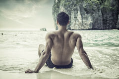 Back of young man sitting on beach on edge of the ocean Stock Image