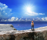 Back of young man standing on rock cliff and looking to sea Stock Photos