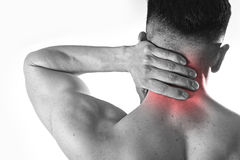 Back young muscular sport man holding sore neck touching massaging cervical area Stock Images