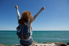 Back of young woman with arms raised to the sky sitting by water Royalty Free Stock Image