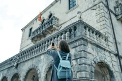 Back of young woman with blue backpack takes pictures of the mus. Eum on the phone Royalty Free Stock Images
