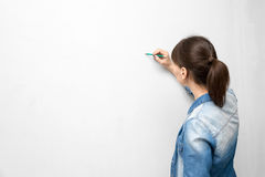 Back of young woman in casual clothes with pencil drawing or wri Royalty Free Stock Image