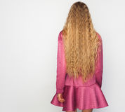 Back of the young woman with long blond curly hair with healthy shine, wearing a purpl dress over a studio background. Indoor Royalty Free Stock Image