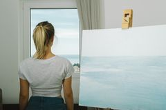 Back of young woman looking at window while drawing painting in. Home studio, art mental therapy Stock Photo