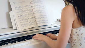 Back of young woman playing the piano in bright room, hand held
