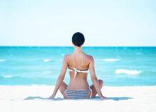 Back of a young woman relaxing on the beach Stock Image