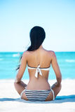 Back of a young woman relaxing on the beach Stock Photos