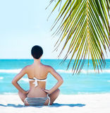 Back of a young woman relaxing on a tropical beach Royalty Free Stock Photo
