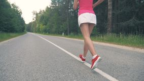 Young healthy woman running along the road. Healthy lifestyle concept. stock footage