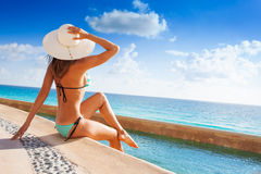 Back of young woman with white hat sitting on pier. Beautiful back of young woman with white hat sunbathes under sun while sitting on stoned pier near to the Stock Photography