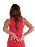 Backache. Young attractive woman suffering from backache. All isolated on white background Stock Photos