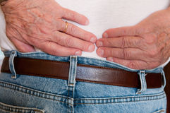 Backache. Close-up of hands of elderly man holding lower back as  in pain Royalty Free Stock Photos