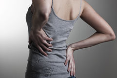 Backache. Woman holding her back in pain Royalty Free Stock Photo