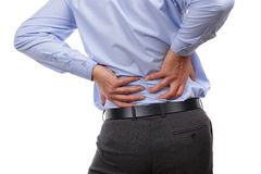 Backache. Concept bending over in pain with hands holding lower back Stock Photos
