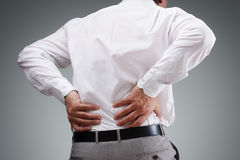 Backache. Concept bending over in pain with hands holding lower back Stock Photography