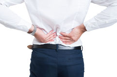 Backache concept with businessman holding hands on lower back Stock Photos